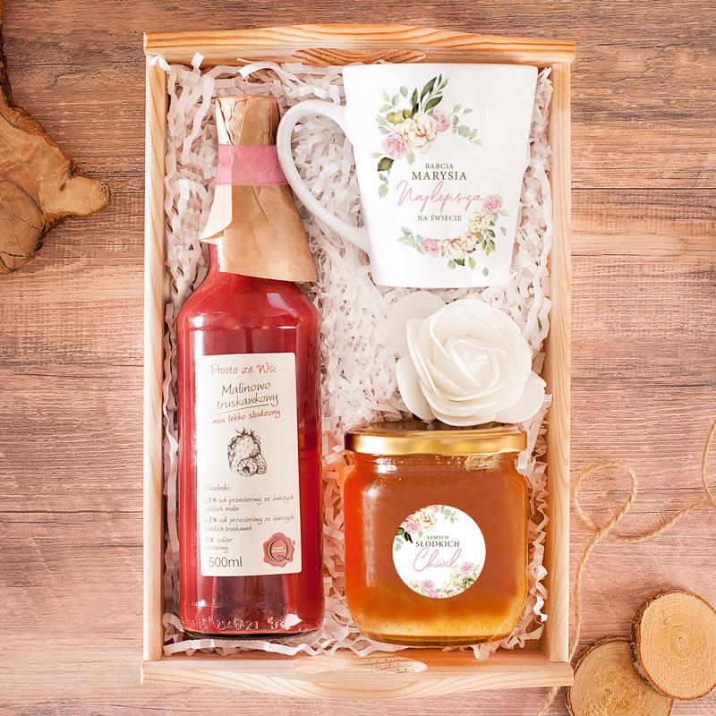 Zestaw prezentowy dla babci. Na drewnianej tacy jest białe wypełnienie, miód z etykietą, kubek z podpisem i kwietnym wzorem oraz owocowy mus w butelce.