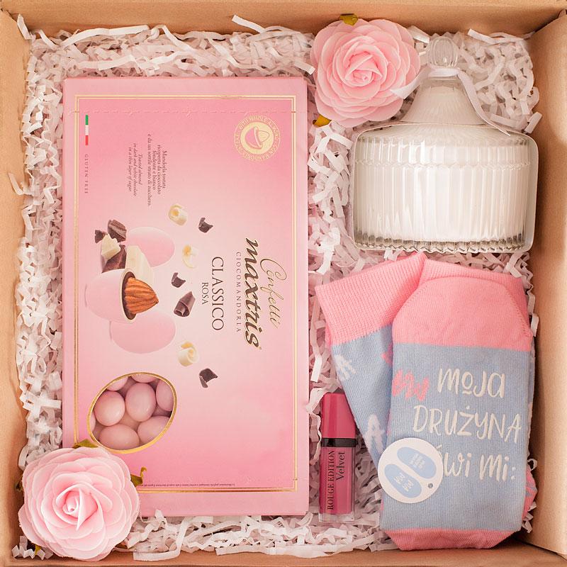 Zestaw prezentowy dla mamy. W kraftowym pudełku są różowe migdały, skarpetki z zabawnym napisem, biała, zapachowa świeczka i błyszczyk do ust. Pudełko wypełnione białym sizalem. Piękny zestaw dla mamy.