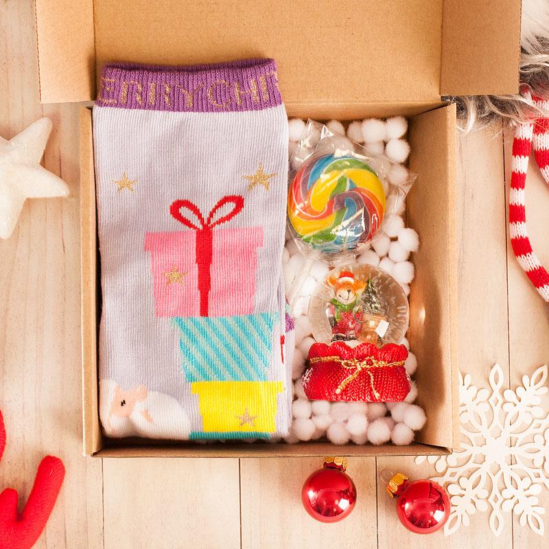 Zestaw prezentów w pudełku z pluszowym konfetti na dnie. Środek wypełniają skarpetki świąteczne, figurka - kula śnieżna oraz słodki lizak.