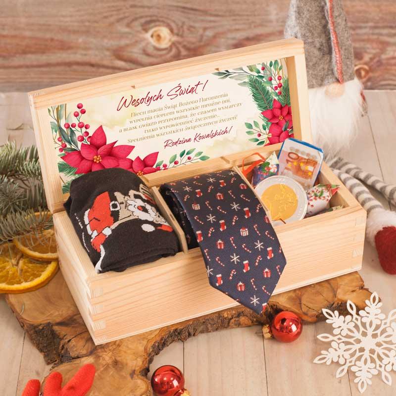 Drewniana skrzynka z trzema przedziałkami, w których znajdują się męskie skarpetki, krawat, słodycze. Na wewnętrznej stronie wieczka znajduje się kartka z personalizowanym życzeniami na Boże Narodzenie.