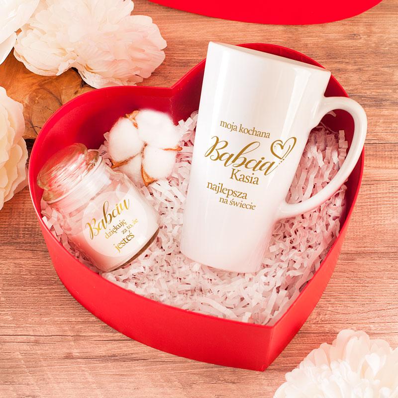 Zestaw prezentowy dla babci w pudełku w kształcie serca. Wewnątrz znajduje się wysoki kubek do latte z imieniem oraz zapachowa świeczka z etykietą na której jest napis dziękuję, że jesteś.