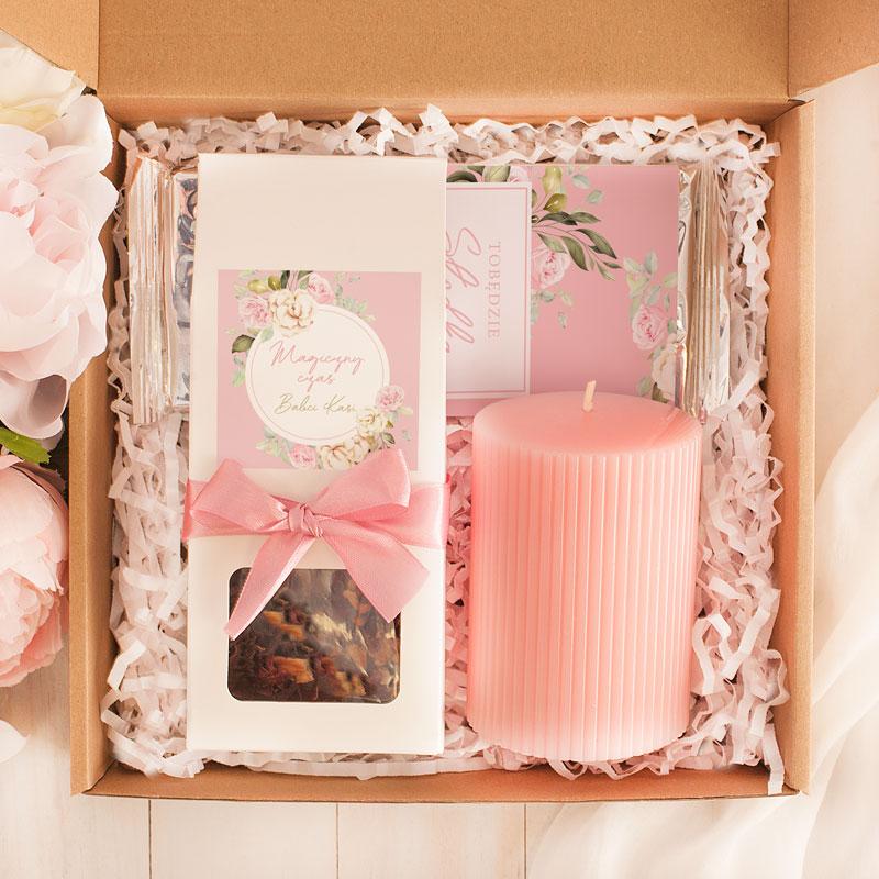 Zestaw w brązowym pudle z konfetii na dnie, z różową świecą, czekoladą i herbatą suszoną z etykietami z motywem róży i personalizacją.
