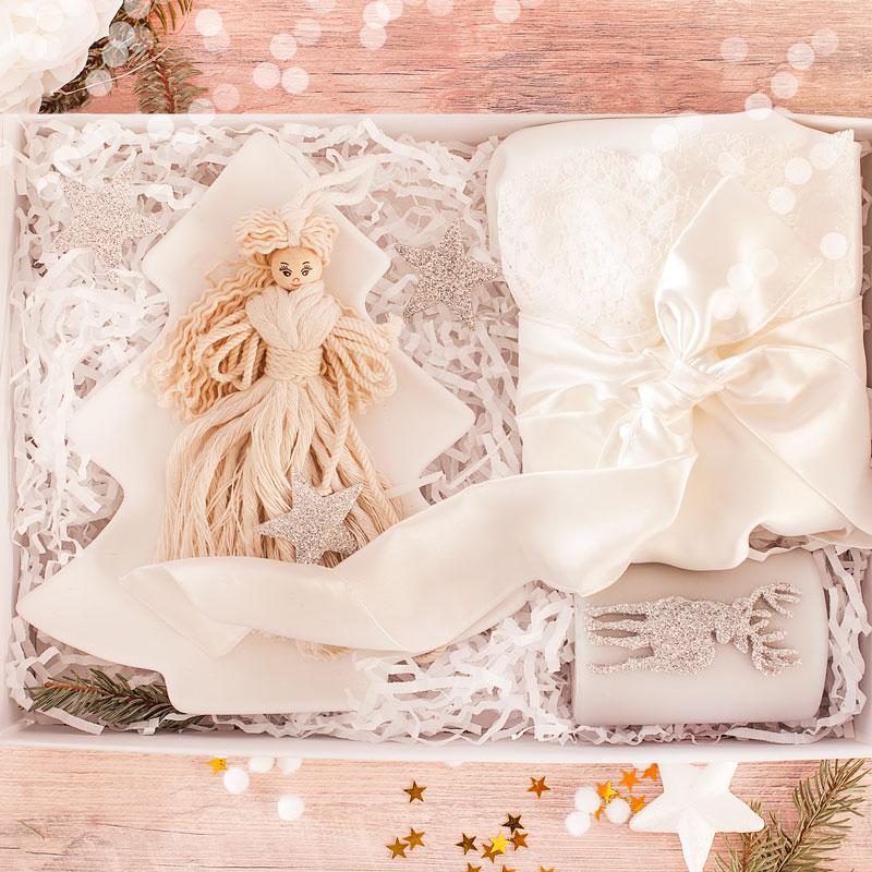 Pudełko z prezentami dla kobiety. W zestawie szlafrok, świeczka, laleczka i zimowa podstawka.