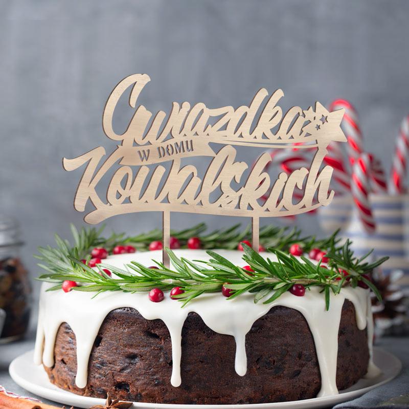 Drewniany topper z nazwiskiem rodziny i napisem Gwiazdka w domu, na dwóch patyczkach do wbicia na powierzchnię ciasta.