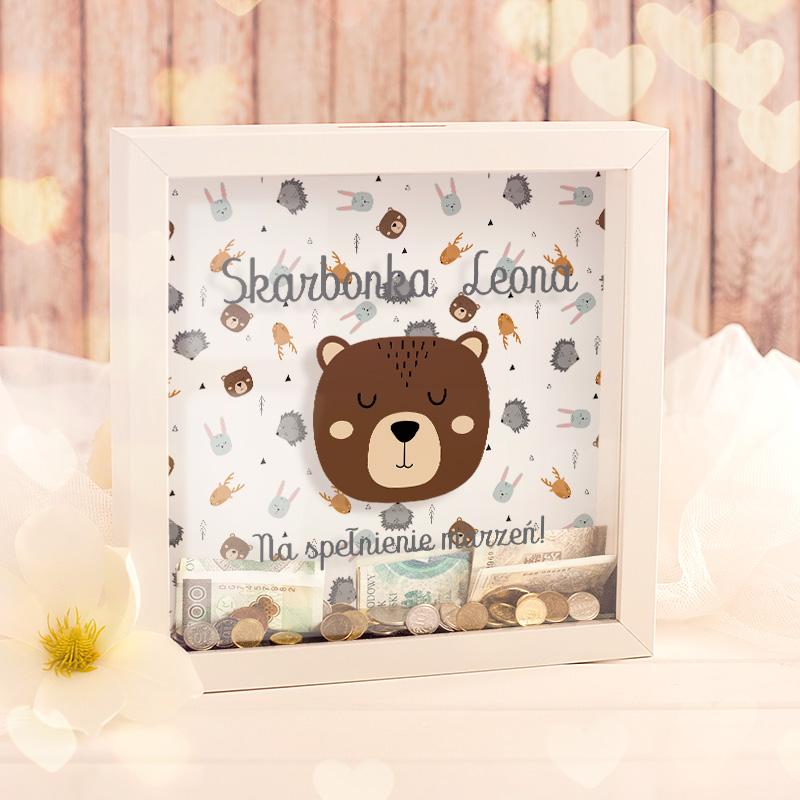 Skarbonka w kwadratowej ramce ze szklaną szybką. W środku jest tło w kolorowe zwierzaki, na zewnętrznej szybce widnieje niedźwiadek oraz napis z imieniem skarbonka na spełnienie marzeń.