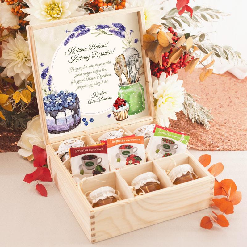 Drewniana skrzynka z personalizowanymi życzeniami dla Babci i dziadka oraz spiżarnianym wyposażeniem czyli dżemikami, miodem i herbatą. Skrzynka zawiera 9 przegródek.