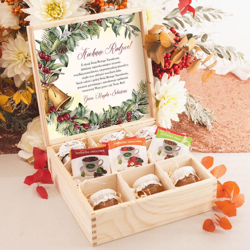 Drewniana skrzynka z miodami, dżemami i herbatą oraz świąteczną kartką na wieczku, na której znajdują się personalizowane życzenia.