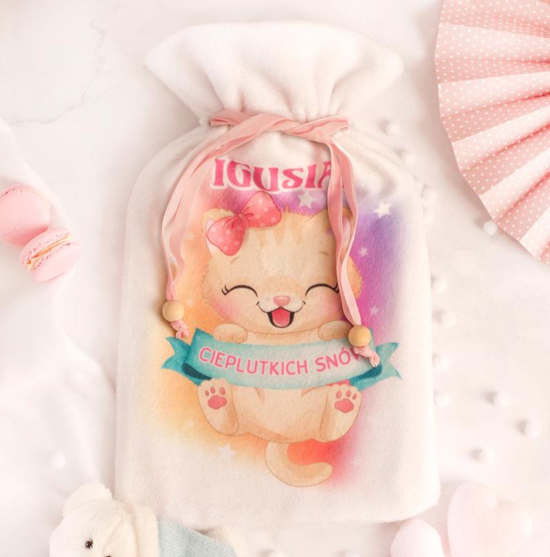 """Termofor w białym woreczku splecionym różową wstążką z drewnianymi koralikami na zakończeniu. Na białym materiale z polaru jest kolorowa grafika z wesołym kotkiem. Trzyma on w łapkach niebieską szarfę z napisem """"Cieplutkich snów"""". Nad kotkiem jest imię dziecka."""