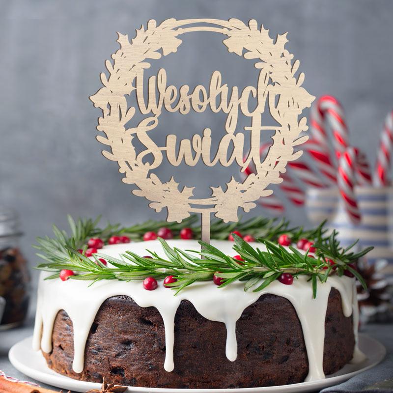 Drewniany topper na tort w środku wianka z napisem Wesołych Świąt.