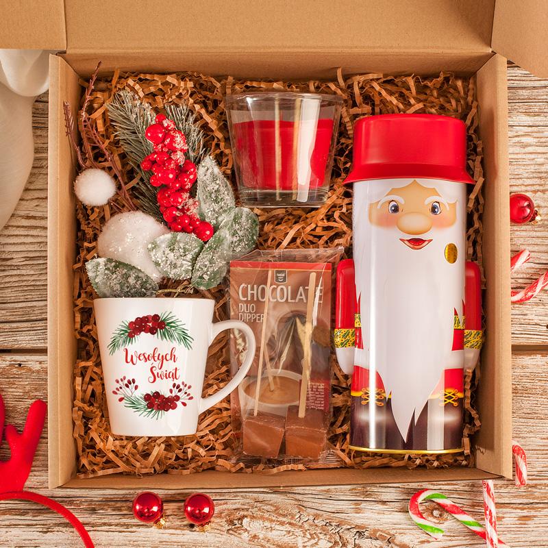 Zestaw prezent świąteczny rozgrzewające upominki czyli kubek, gorąca czekolada, herbata w ozdobnym pudełku, świeczka i świąteczny stroik.