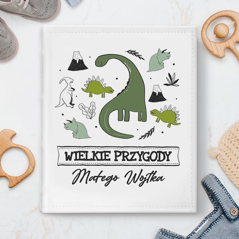 Album do zdjęć dziecka posiada personalizowaną okładkę. Wzbogacony jest o grafikę z kolekcji Dinozaury. Całość zachowana jest w jasnej kolorystyce, z zielonymi elementami.