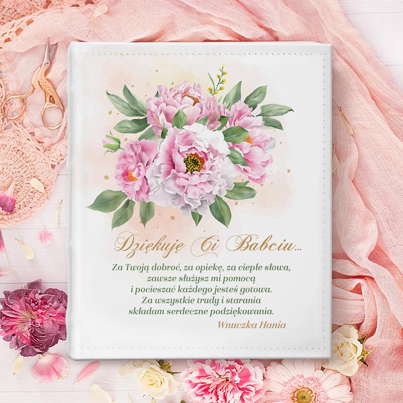 Album pamiątkowy do wklejania zdjęć prezent dla babci. Na białej okładce jest bukiet różowych piwonii, a pod spodem długie życzenia dla babci i miejsce na Twój podpis.