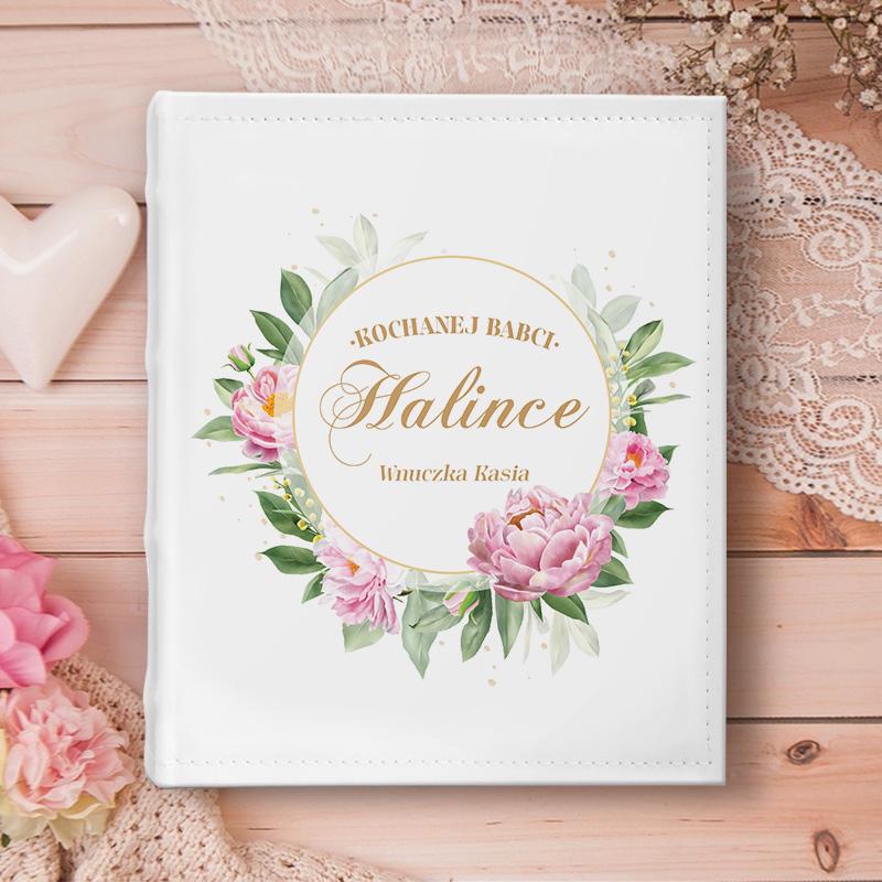 Album na zdjęcia z personalizowaną okładką na której znajdują się kwiatowe zdobienia oraz dedykacja Kochanej babci z imieniem i podpisem.