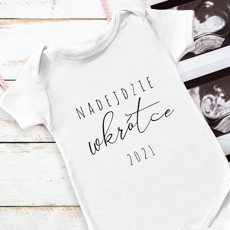 Białe dziecięce body dla niemowlaka wzbogacone o czarny nadruk. Idealnie sprawdzi się, aby poinformować bliskich o ciąży. Body zawiera napis Nadejdzie Wkrótce, wraz z rokiem.