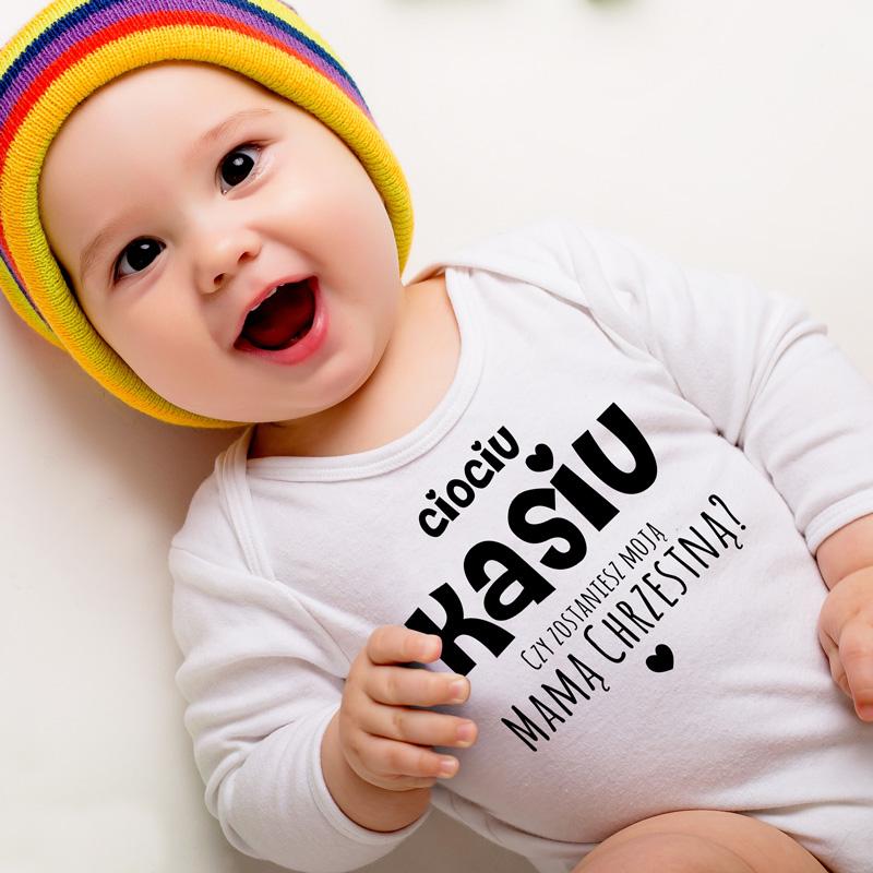 Body pytanie do rodziców chrzestnych z imieniem cioci lub wujka. Napis jest czarny, znajduje się na białym materiale ubranka.