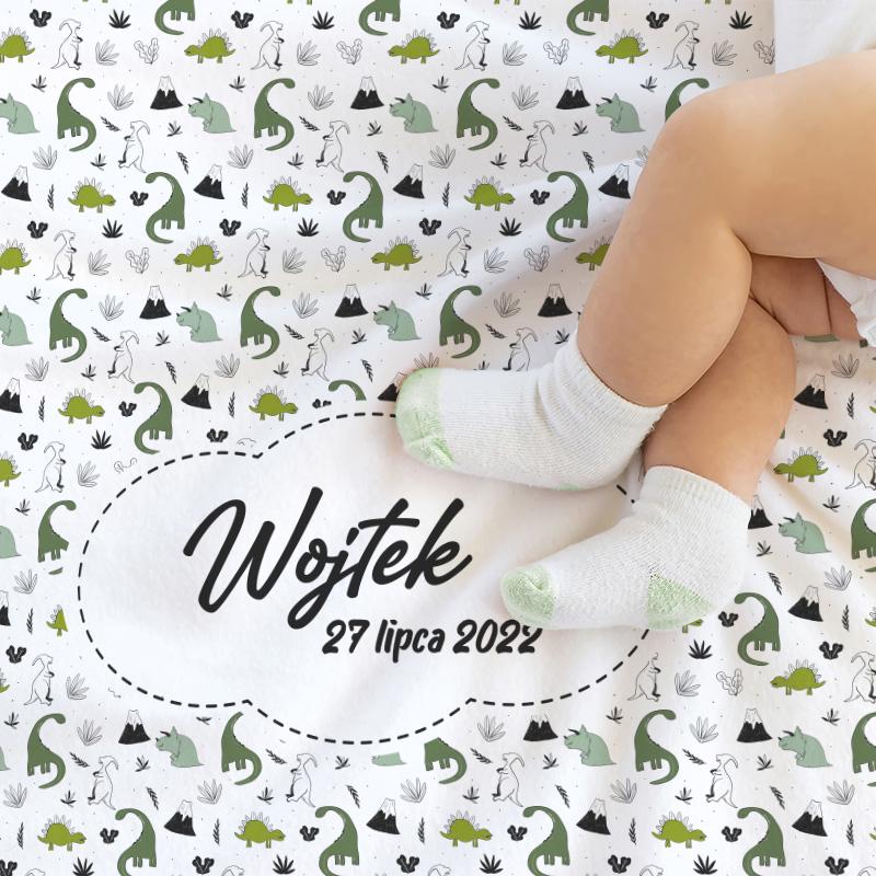 Biały kocyk dziecięcy z grafiką pełną dinozaurów w kolorze zielonym. Na środku biała, graficzna chmurka z miejscem na personalizację - imię i datę urodzenia.