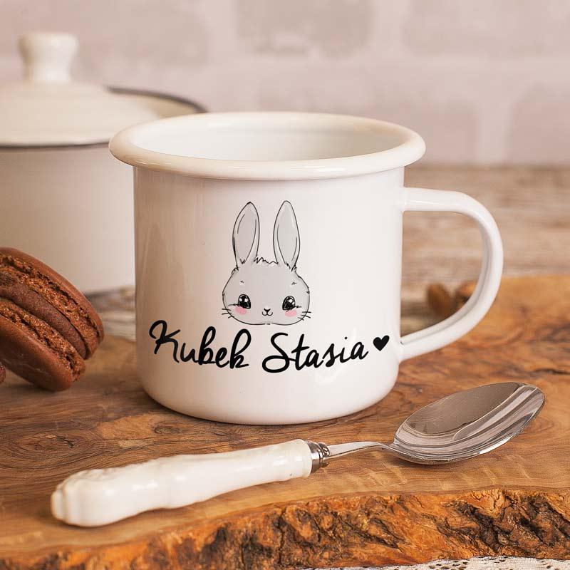 Kubeczek metalowy z rantem i wygodnym uszkiem. Jest biały, na jego froncie znajduje się grafika z króliczkiem oraz napis kubek + imię dziecka.