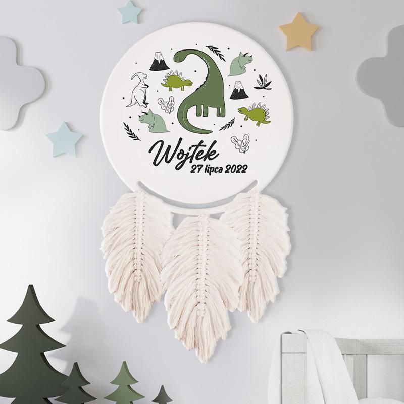 Łapacz snów z imieniem to efektowna dekoracja do pokoju dziecka. Nadruk z dinozaurami znajduje się na białej tarczy. Poniżej umieszczone są piórka, wykonane metodą makramy.