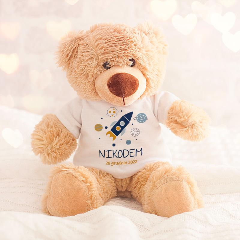 Miś pluszowy posiada miękkie futerko, ubrany został w białą koszulkę, na której widnieje imię chłopca oraz grafika przedstawiająca rakietę kosmiczną oraz planety.