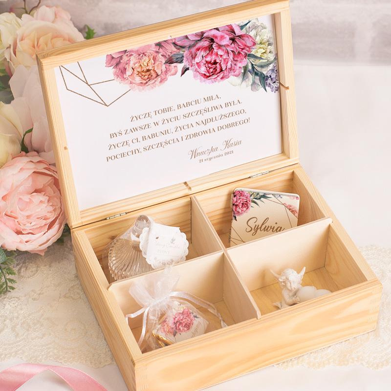 Skrzynka z drewna z przegródkami, a wewnątrz nich znajdują się upominki dla babci oraz karta z życzeniami.