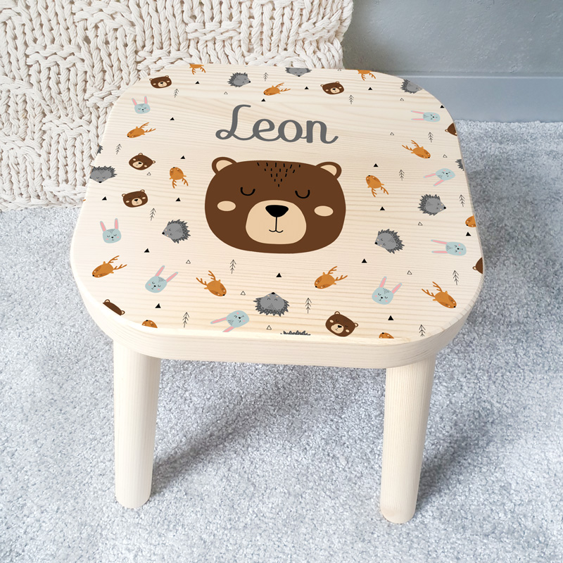 Taborecik dziecięcy z drewna, stojący na czterech, odkręcanych nóżkach. Na wieczku stołka jest grafika z kolekcji Skandynawskie Zwierzątka oraz imienna dedykacja dziecka.
