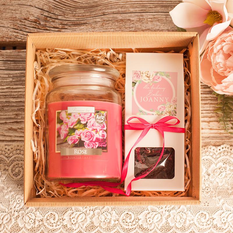 Zestaw aromatyczny dla babci w kraftowym, kartonie znajduje się duża świeca o różanym zapachu oraz pudełko z herbat.ą hibiskus