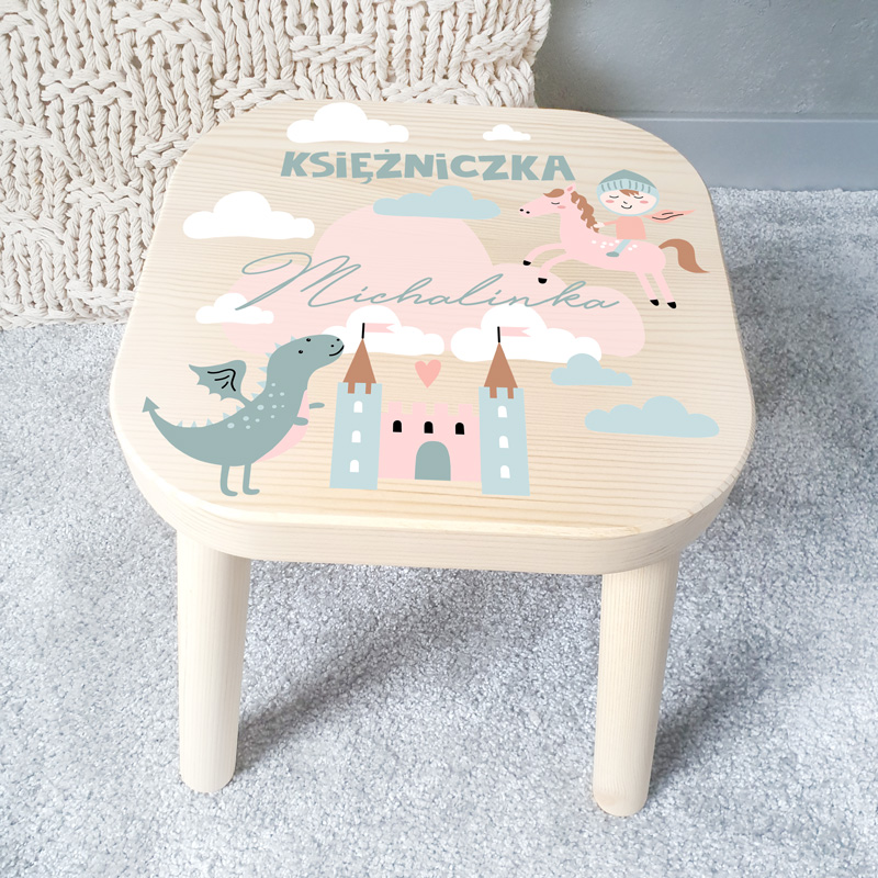 Taboret dziecięcy drewniany wykonany jest z jasnego drewna. Na siedzisku umieścimy kolorową grafikę, która pochodzi z kolekcji Bajkowe Królestwo. Całość zachowana jest w pastelowej kolorystyce.
