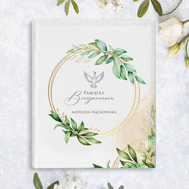 Album na zdjęcia z dedykacją imienną oraz napisem Podarunek na Bierzmowanie. Napisy znajdują się w środku dekoracyjnej obręczy z zielonymi listkami, w towarzystwie białej gołębicy.