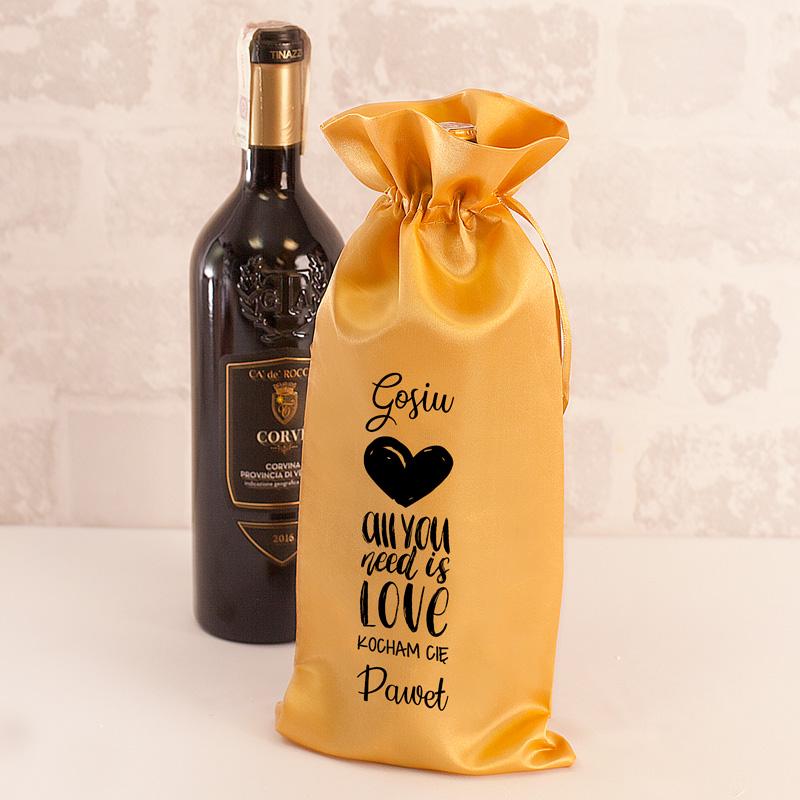 Worek na butelkę z nadrukiem w złotym kolorze. Na satynowym worku widnieje nadruk z napisem all you need is love.
