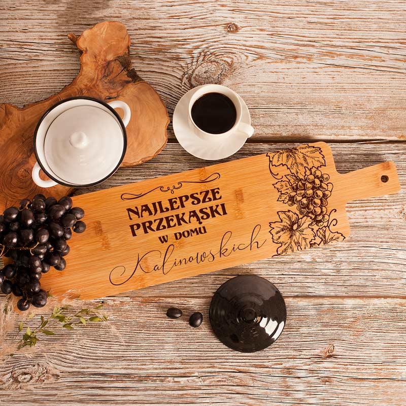 Podłużna deska z grawerem do krojenia i na przekąski z nadrukiem w postaci winogronowych kiści i nazwiskiem rodziny.