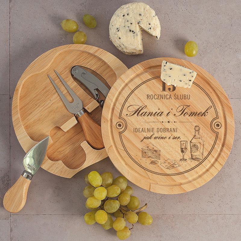 Zestaw do serwowania serów w postaci okrągłej deski z przesuwanym mechanizmem, z futerałem na sztućce do przekąsek oraz grawerem na rocznicę ślubu.