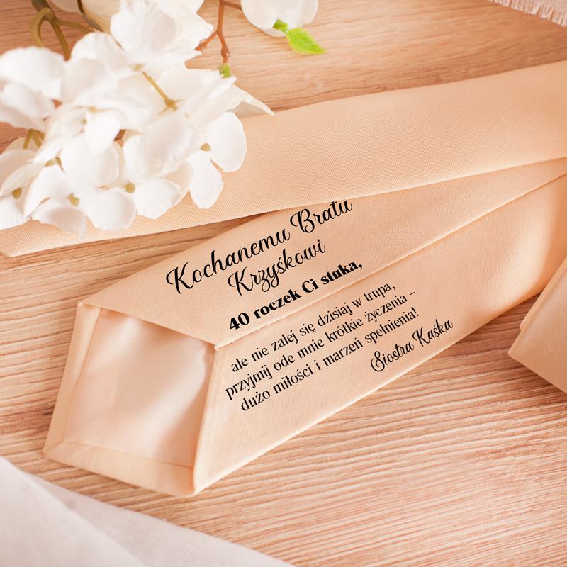 Kremowy krawat z dedykacją od wewnątrz dla brata. Napis zawiera życzenia, imię brata oraz podpis od kogo jest prezent.