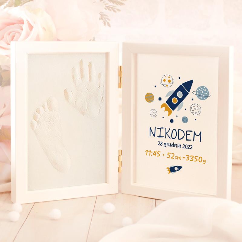 Podarunek z okazji narodzin - metryczka dziecka w białej ramce z motywem kosmicznej przygody i danymi z dnia narodzin po jednej stronie ramki. Druga strona to miejsce na umieszczenie odcisków dziecka, które należy wykonać w masie gipsowej, która jest częścią zestawu.