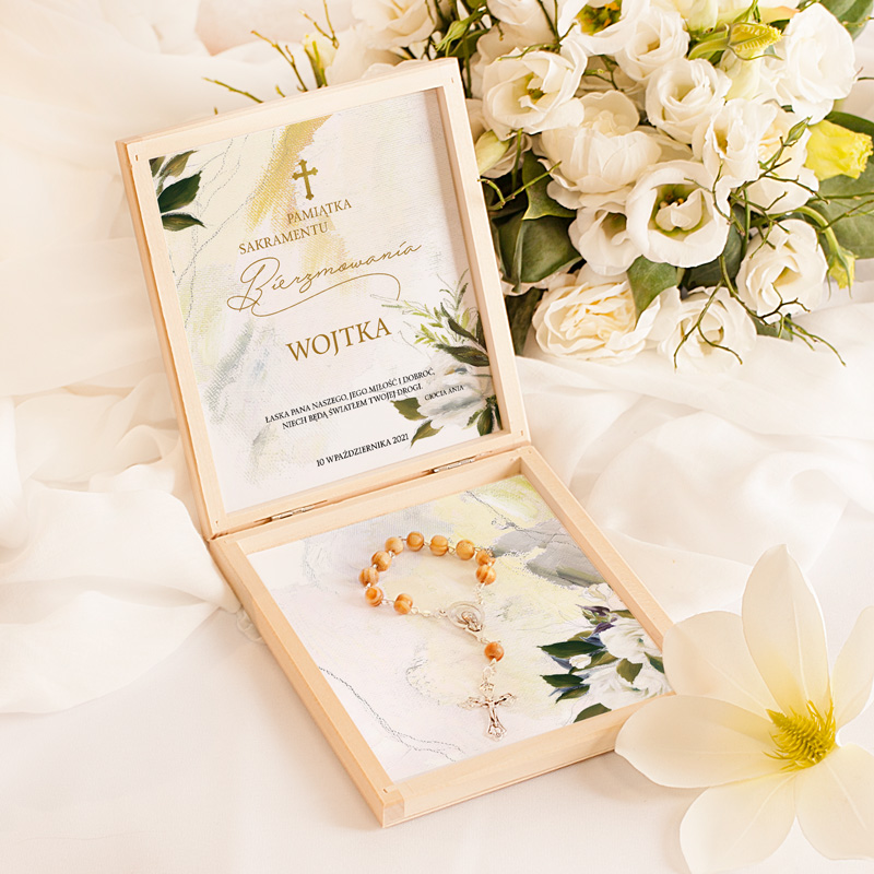 Pamiątka bierzmowania w postaci kwadratowej płaskiej szkatułki z dziesiątką różańca w środku oraz z dekoracyjnymi kartami, na których znajdują się życzenia, podpis i data.