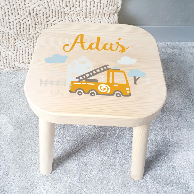 Taboret dziecięcy drewniany z imieniem dziecka w jasnej kolorystyce. Na siedzisku znajduje się grafika, która przedstawia wóz strażacki.