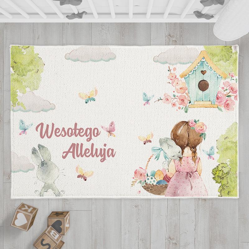 Dekoracyjny dywanik z uroczą grafiką z dziewczynką, która ma koszyk z pisankami i zającem na ramieniu. Na środku dywanika znajduje się napis Wesołego Alleluja!
