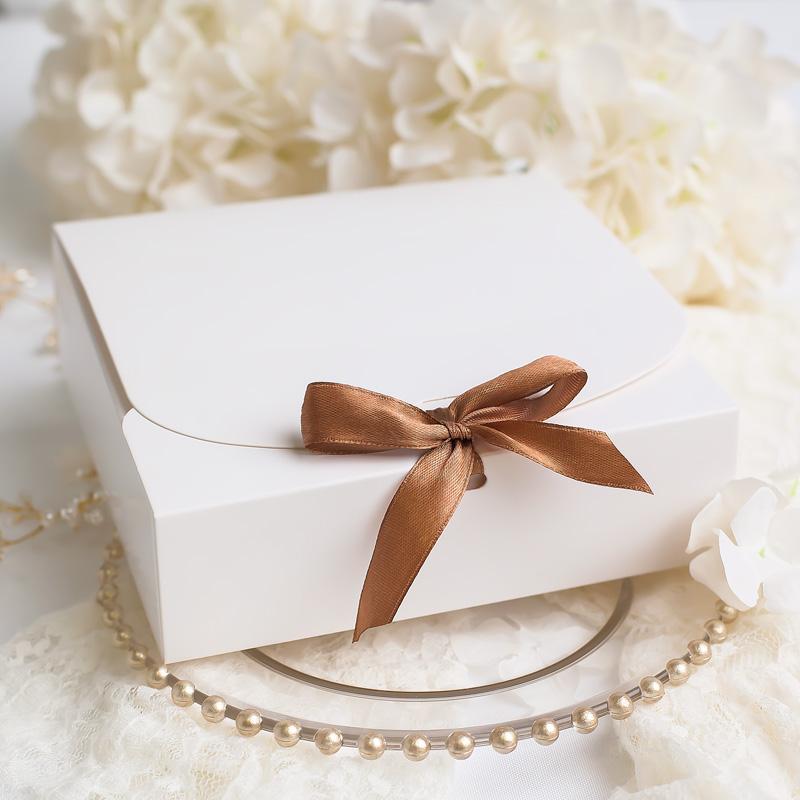 Ozdobne pudełko do zapakowania prezentu z satynową wstążką w brązowym odcieniu.