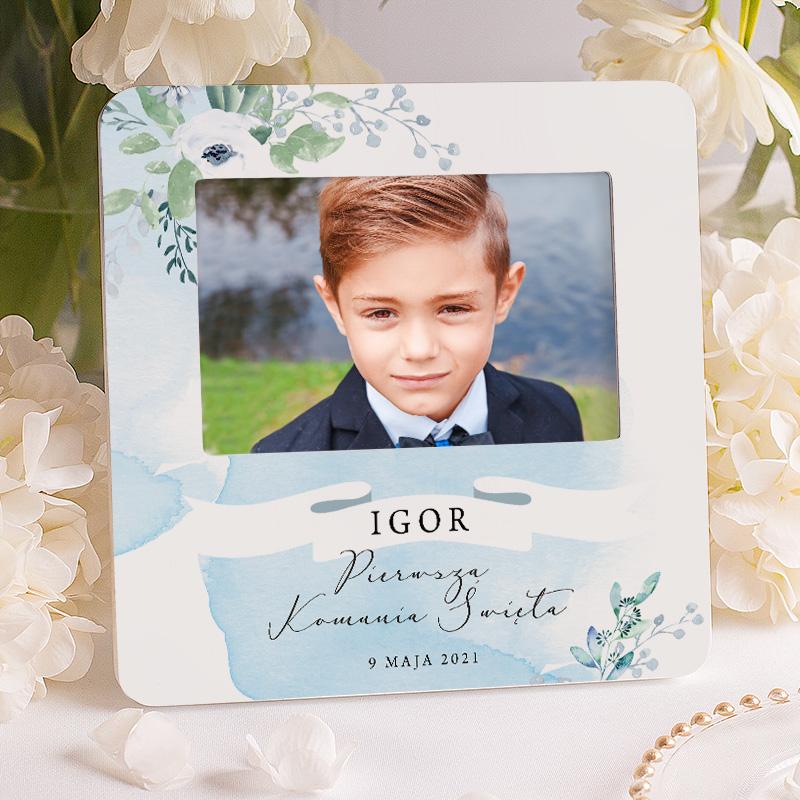 Personalizowana ramka na fotografię z sesji komunijnej, na której znajduje się imię dziecka i data uroczystości, wkomponowana pod napisem Pamiątka Pierwszej Komunii Świętej.