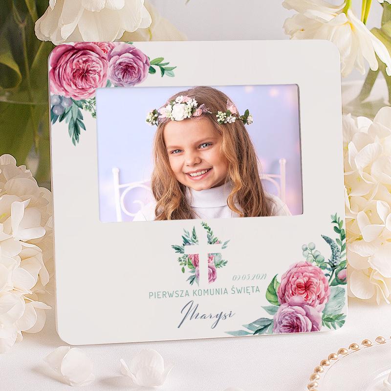 Ramka na zdjęcie z perosonalizowaną dedykacją na komunię z imieniem dziecka oraz datą sakramentu. Ramka jest ozdobiona różowymi kwiatami.