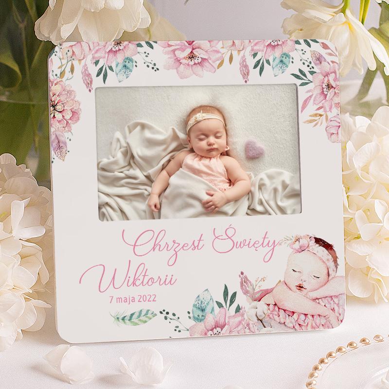 Ramka na zdjęcie z imieniem dziecka datą i napisem chrzest święty. Ponadto na ramce znajduje się motyw z różowymi kwiatami i uroczą dziewczynką.