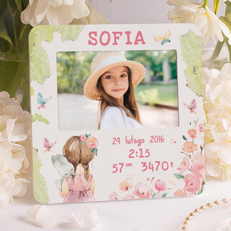 Ramka na prezent urodzinki dziewczynki. Na ramce znajduje się obrazek z dziewczynką która trzyma na ramieniu zajączka oraz personalizowane podpisy w formie metryczki dziecka.