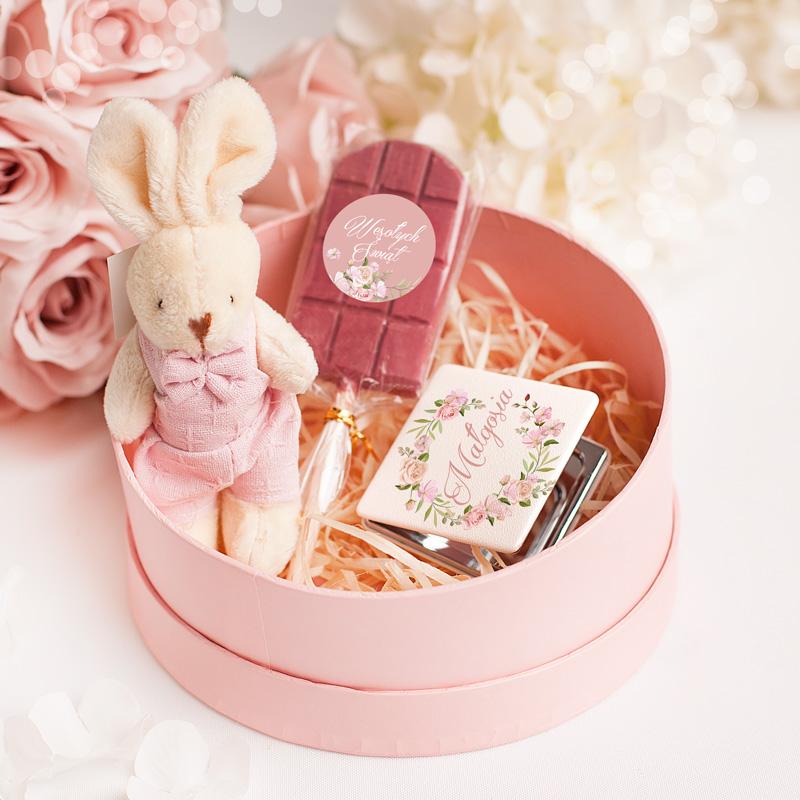 Różowy zestaw wielkanocny upominków dla dziewczynki. W różowym pudełku znajduje się pluszowy zajączek, lizak o smaku malonowej czekolady oraz lusterko z imieniem.