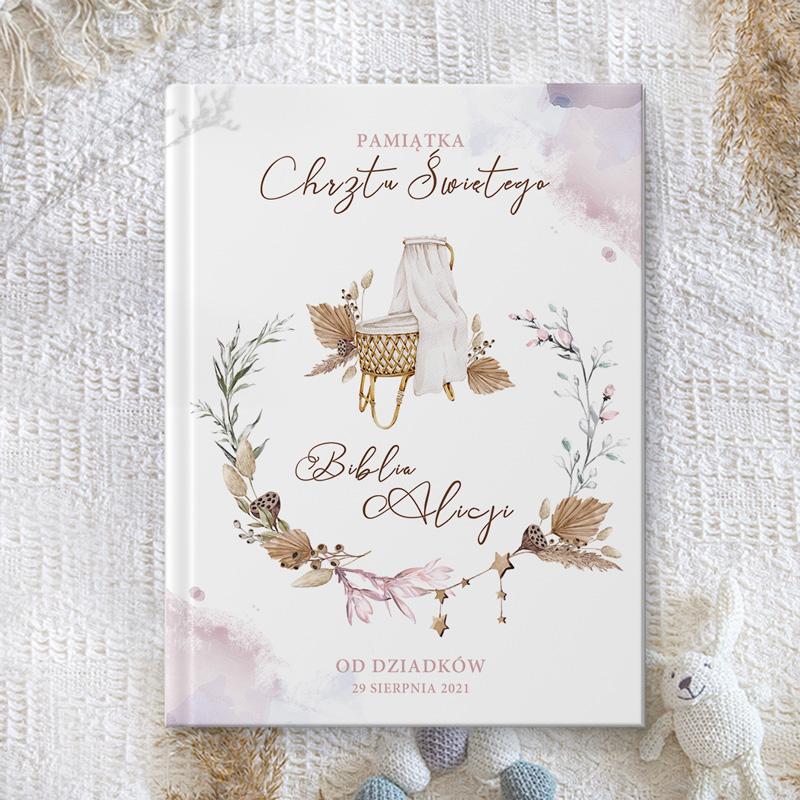 Personalizowana Biblia z imieniem dziecka na okładce, datą i podpisem i kołyską z wikliny.