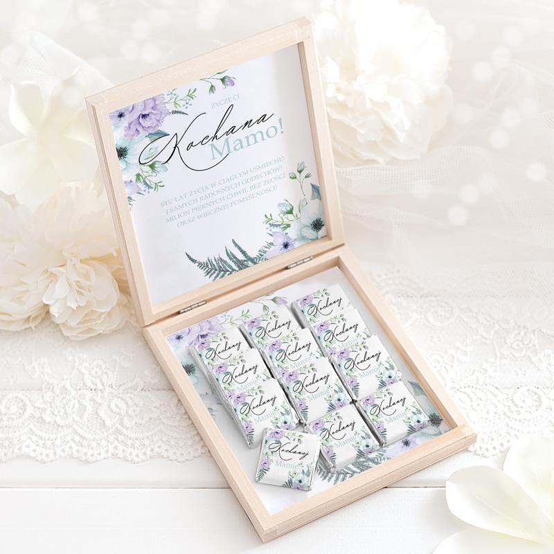 Bombonierka z czekoladkami dla mamy, w drewnianej szkatułce. W środku znajduje się 12 belgijskich czekoladek z dedykacją Kochanej Mamie. W środku znajduje się także na wieczku ozdobna kartka z życzeniami i dekoracyjnymi kwiatami.