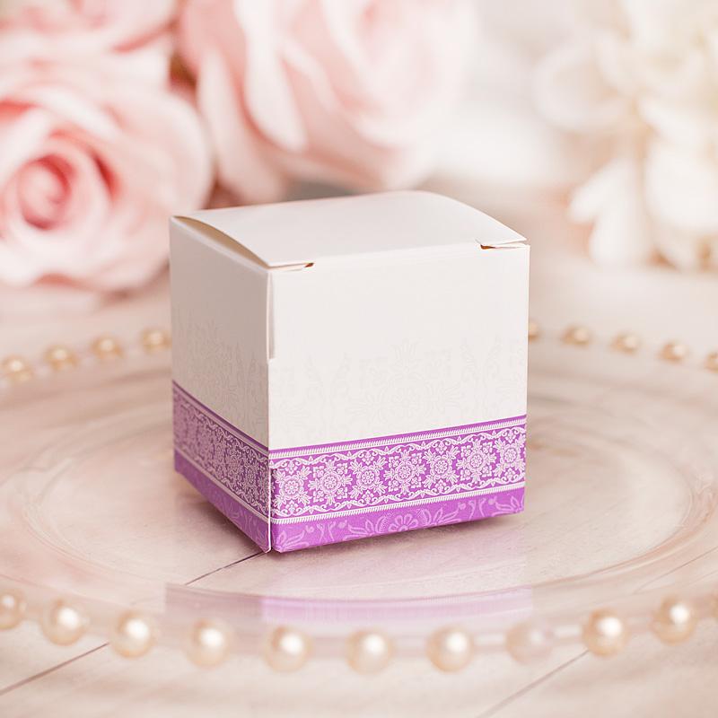 Pudełka na upominki dla gości w białym kolorze, z fioletowym zdobieniem.