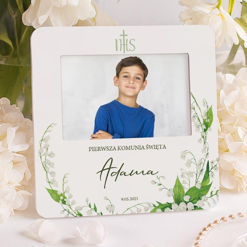 Ramka na zdjęcie z imieniem dziecka, napisem Pierwsza Komunia Święta i datą. Wokół napisów znajdują się białe konwalie.