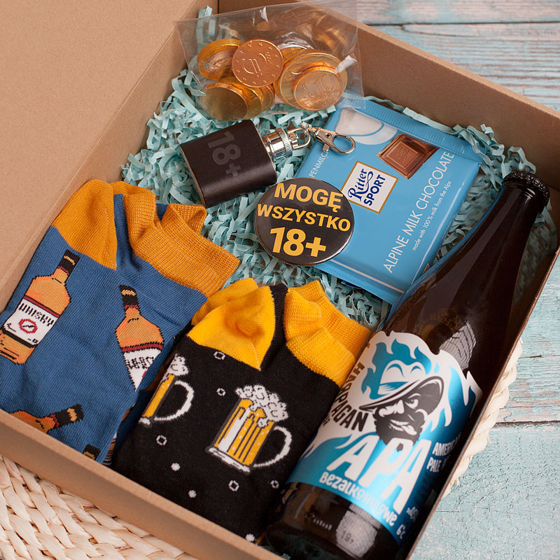 Zestaw urodzinowy na 18 urodziny w kraftowym pudełku. Wnętrze wypełniają skarpetki, piwo bezalkoholowe, piersiówka i otwieracz.