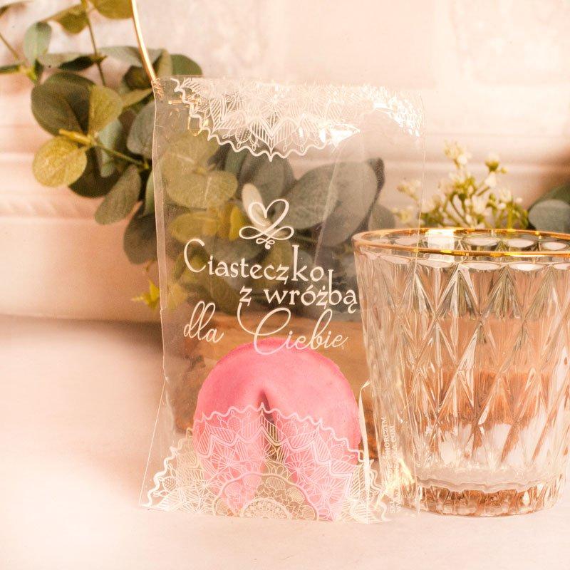 Różowe ciasteczko z wróżbą w przezroczystym opakowaniu z dekoracyjną koronką i napisem Ciasteczko z wróżbą dla Ciebie.