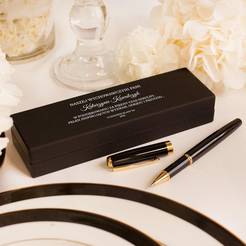 Dwa czarne długopisy w czarnym etui z kremowym środkiem. Na zewnątrz etui znajduje się dedykacja dla wychowawcy prezent na koniec roku szklonego.