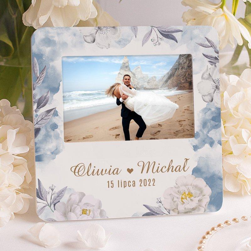 Personalizowana ramka na zdjęcie ślubne dla małżeństwa. Na ramce znajduje się zdobienie z kwiatami i niebieskimi akcentami oraz imionami i datą.